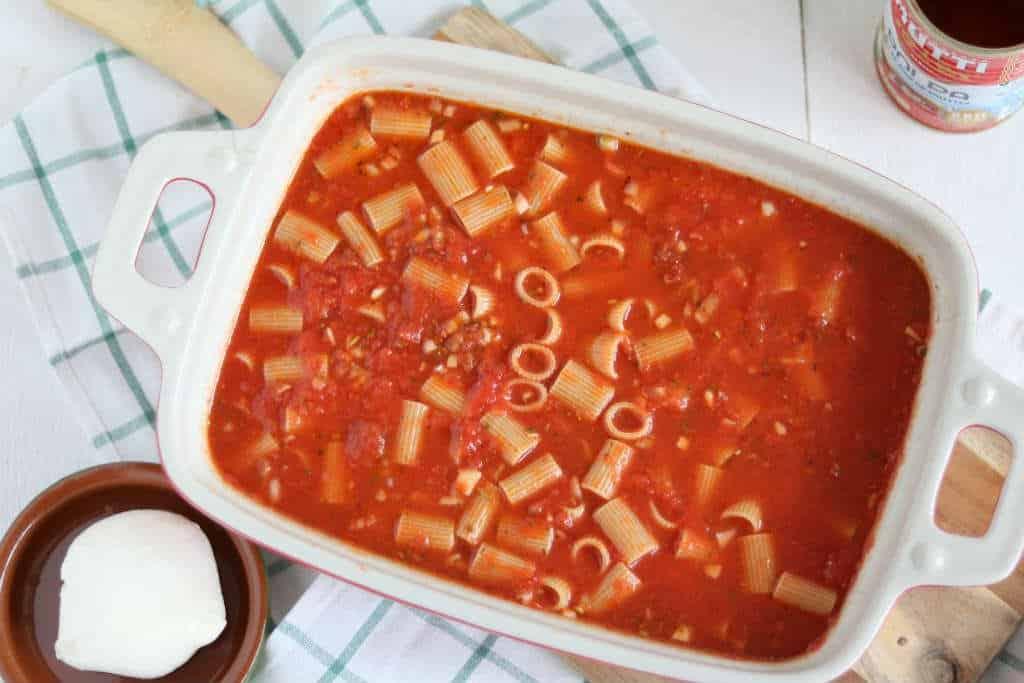 Vegetarische pasta ovenschotel, alle ingrediënten ongekookt in de ovenschaal.