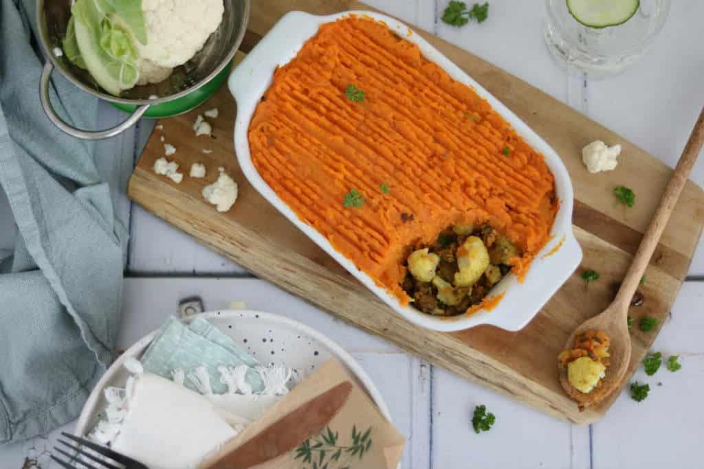 Ovenschotel met bloemkool en zoete aardappel. Dit ovenschotel recept heeft een Oosterse twist. Vervang het gehakt door linzen voor een vegetarisch gerecht.